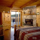 Master bedroom with river rock fireplace in corner and hardwood flooring, log bed with southwestern wool blanket views out french doors to Colorado mountains.