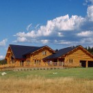 Exterior of custom log home with attached garge and large front deck lined with log railings.