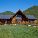 Exterior of ranch style handcrafted log home set in Colorado meadow with mountains behind.