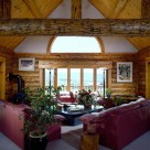 Interior of rustic log home living room with red leather couches on carpet. Log wall with round top window in white gable end.