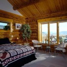 Master bedroom in handcrafted log home with wicker chairs set next to large windows looking out to Colorado mountains.