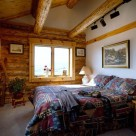 Guest bedroom with sloping pine ceiling in log cabin with track lighting mounted to log beams above.