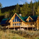 Three chamber log home with steep roof pitches and green metal roof set on full basement in Colorado forest. Large windows fill front wall of great room and doghouse dormers on either side break up roof lines.s
