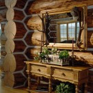 Close up photo of log home interior with massive chinked log wall and corner. Ornate table with drawers is set below large woodframed mirror with elk antlers on either side.