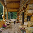 Covered porch at end wall of handcrafted log home. Log posts and beams support cathedral roof above wood benches and flowers in this rustic log home.