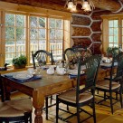 Dining room in handcrafted log home with large wooden table and green highback wood chairs look out through large windows onto deck with log railings and forest beyond.