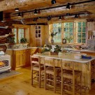 Kitchen in custom log home with vermont castings wood stove, center island with wine rack on end and track lighting above attached to massive log ceiling joists.