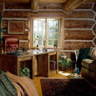 Office with oak table and high back red leather office chair in log home built with massive handpeeled logs with white chinking material between logs.