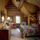 Loft bedroom with iron bedframe set in dormer of handcrafted log home.