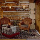 Sitting area with wicker chars and ottoman on area rug set against log wall with massive logs.