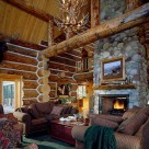 Great room with cozy chairs on green carpet view large riverrock fireplace in Handcrafted log home. Antler chandelier hangs in front of massive log supporting cathedral ceiling..