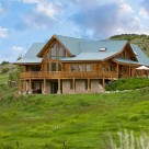 Exterior view of large 3 chamber custom log home with green metal roof set on walkout basement on green sloping land.
