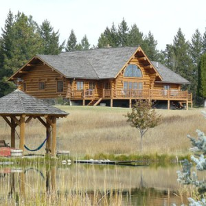 Exterior of log home viewed across pond with log gazebo