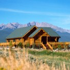 Exterior view of handcrafted log home with wrap around deck, log railings and green roof framed by Colorado Rocky mountains in background.