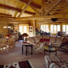 Interior great room of handcrafted log home with cathedral ceilings with log truss and log purlins above large white sectional couch on carpeting.