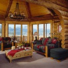 Colorado rocky mountains viewed through large pine trimmed windows in sunroom of handcrafted log home with log archway and exposed log rafters and knotty pine ceiling.s