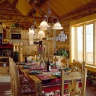 Large wood dining table with navajoe table runner in handcrafted log home with cathedral ceilings.