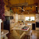 Log home kitchen with light brown tile floors, custom pine cabinets and island. Unique log lighting frame suspended by chains from cathedral ceiling.