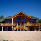 Exterior of custom log home duplex with log truss at covered entry and large decks with log railings. Semicircle windows on either side of center.