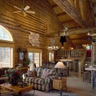 Extrodinary log home greatroom with soaring ceilings and massive log trusses. Fabric love seat sits on Navajoe area rug and mountain lion mount is perched on log beam above with antler chandelier lighting the space.