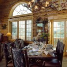 Custom wood dining table with bark on edges and bark on log dining chairs with antler chandelier above in handcrafted log home with french doors and sunrise grid arched window.
