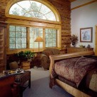 Master bedroom in handcrafted log home with cozy chairs large Armoire and twelve foot wide window with radius top showing view of Colorado forest.