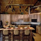 Custom kitchen with wood cabinetry and large breakfast bar with lovely bar stools in handcrafted log home. Unique log frame with spot lights attached is suspended by chains