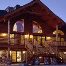 Twilight photo of amazing log duplex set on massive river rock faced lower level with grand entry framed by log pillars and log truss. Radius top windows backlit showing interior of homes.