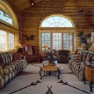 Handcrafted log home living room with massive french doors and semicircle windows above. Soaring cathedral ceiling above large sofa's set on indian style area rug.