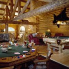 Amazing game room in custom log home with poker table and log framed cuatom pool table. Enormous log truss and log beams support cathedral roof above and blackbear rug is mounted on log wall.