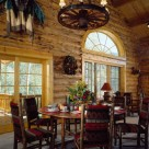 Large wood dining table with cozy dining chairs in Log home with french doors, wagon wheel chandelier and sunrise grid half circle window above door.