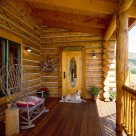 Entry porch on handcrafted chink style log home with wicker loveseat and white dog lying in front of Specialty Woodworks oval window pine door.