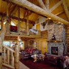Handcrafted log home great room with cathedral ceilings, stone fireplace with log mantle, log truss and log posts supporting exposed log purlins
