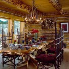 Large log slabe dining table with highback log chairs in chink style log home with antler chandelier over table and large windows trimmed in pine.
