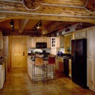 Custom kitchen cabinets and island in kitchen with hardwood floors in chink style log home.