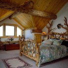 Custom log bed with handcarved fish inlaid into headboard in loft bedroom with gable dormer and exposed log purlins with pine ceiling boards.