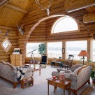 Interior log home living room with massive log arch framing bay windows with arch window above. Upholstered sofa and loveseat with end table sit on white carpet.