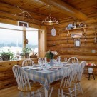 Dining room in handcrafted log home with country kitchen table and chairs set on hickory wood floors in front of large bay window viewing cold winter day outside.