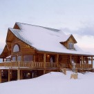Exterior of custom log home covered in snow with bay windowed front, gable dormer and covered porch with log rails.