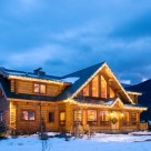 Twilight photo of custom log home with steep center gable filled with glass, shed dormers on either side and bright sunroom in front.