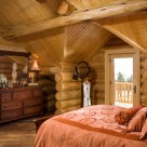 Loft bedroom in handcrafted log home with gable dormer and antique dresser.