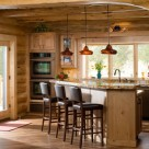 Large granite topped breakfast bar with four leather stools and pendant lighting seen through log archway.