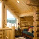 Cozy nook in loft of handcrafted log home with trapezoid window showing view of forest beyond.
