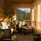 Sunroom in handcrafted log home with cozy chairs and ottoman with views of mountains and forest through lorge windows trimmed in pine.