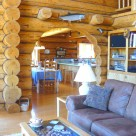 Interior of log home with archway between living room and kitchen