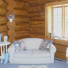 Loveseat in sitting area of handcrafted log home