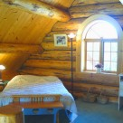 Loft bedroom with archtop window in custom log home