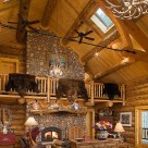 Bear rugs draped over log railings above massive river rock fireplace in full scribe log home with timber frame truss and antler chandelier.