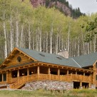 Luxury log home with wrap around porches, bay window with copper trim and river rock patio set in aspen forest below red rock cliffs.