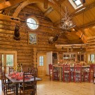 Massive log home kitchen and dining area with timberframe trusses supporting log beams in cathedral ceiling.
